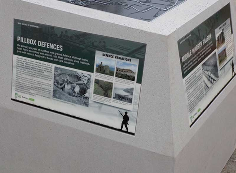 GRP interpretation panels around the side of the concrete marker.