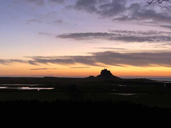 At the beginning of the day as the sun is rising behind Lindisfarne Castle.