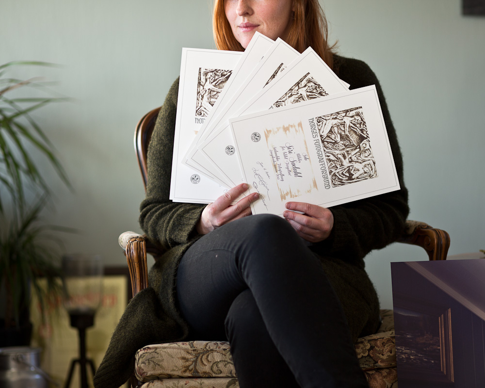 Fotograf Siri Sødahl viser frem diplomene fra laugs konkurransen på Sørlandet