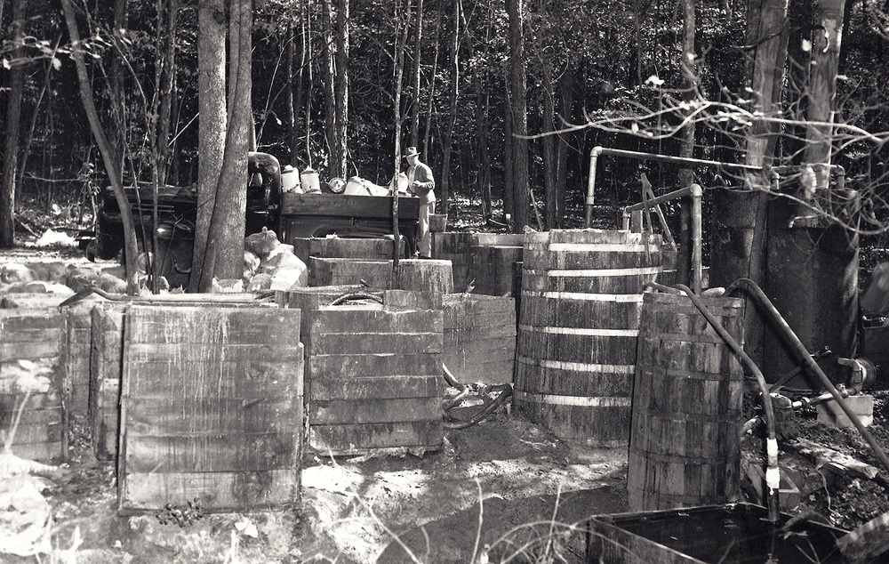 Large steam still operation located in Wilkes County in Call's Section.  Note the 4x4 open wood fermentation boxes on left and the still, burners, thumper, and condenser on right.  The Revenuer in the background looking on to his find.