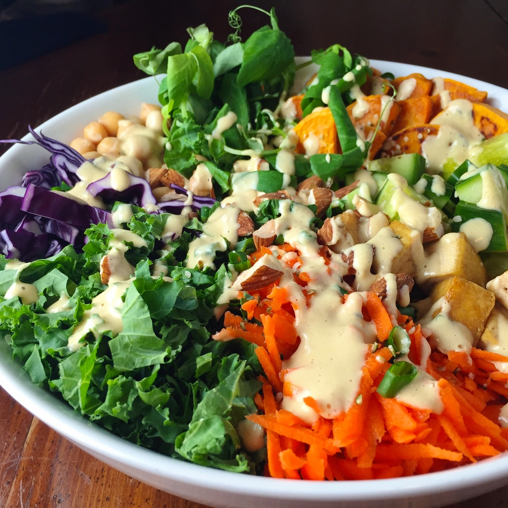 Homemade orange miso tahini dressing is the perfect compliment to this salad, with chopped kale, purple cabbage, cucumber and green onions, toasted almond pieces, grilled sweet potato, fried sesame tofu, grated carrots, chickpeas, pea shoots and hemp seeds on a bed of quinoa.