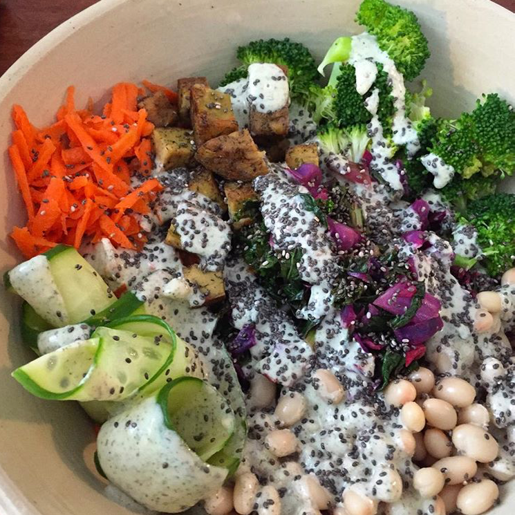 Homemade cashew lemon dill dressing on brown rice, quinoa, steamed broccoli, sautéed cabbage and kale, beans, grated carrots, cucumber, fried tofu cubes and chia seeds.