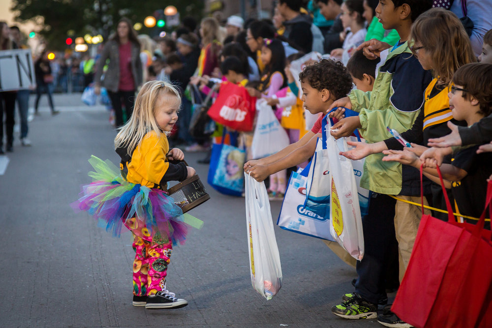 Kids collecting candies during the annual Homecoming Parade event in downtown Iowa City, Oct. 2015