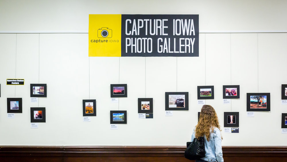 An exhibition-goer examines a photo at the Capture Iowa Photo Gallery opening reception at University of Iowa, April 2015