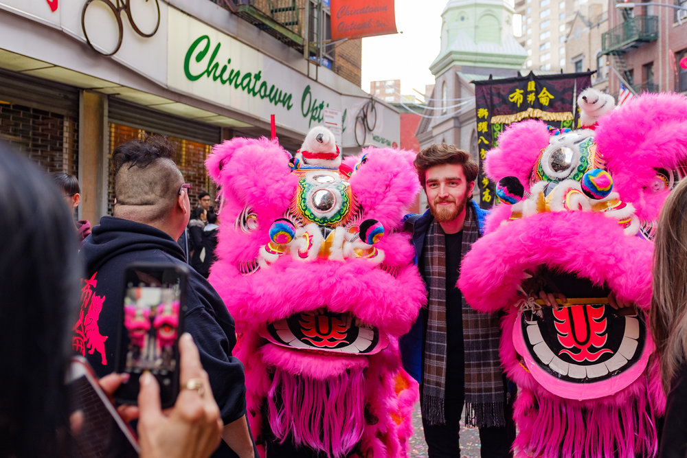 A local posing with Lion Dance performers during a Chinese New Year Celebration Event in Chinatown of Manhattan, in New York City, Feb. 2019
