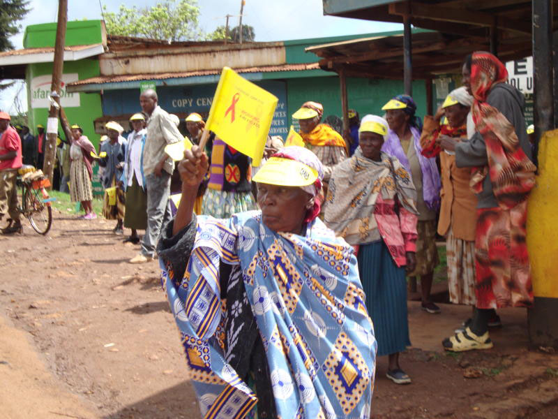 An older woman joins a street match in a campaign against HIV and AIDS among older women in Kenya.