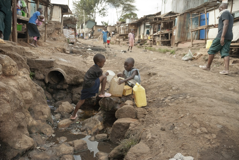 NAIROBI, KENYA -Boys take a water for drinking on a street of Kibera. Kibera is the biggest slum in Africa