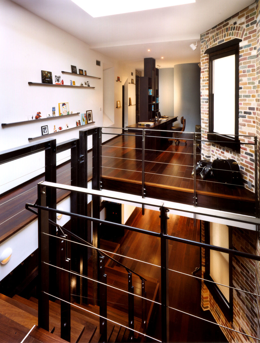 Interior view of duplex designed with custom steel railings. View into the office space featuring wood floors, exposed brick walls, and skylight.