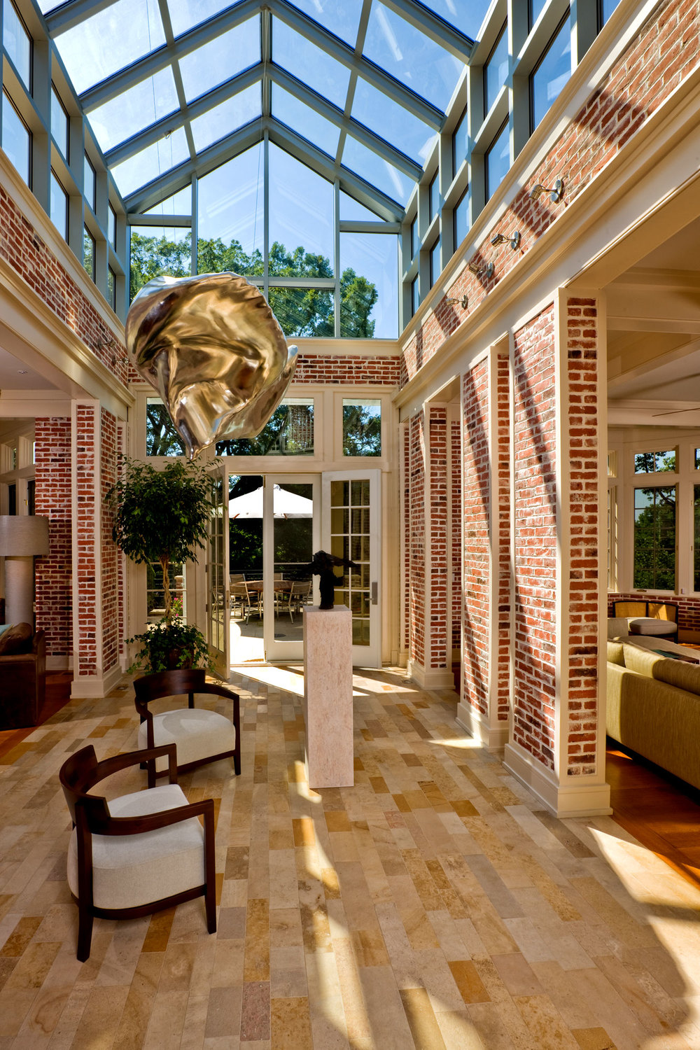 View looking out towards the garden under the monumental glass skylight. Natural light pours in, illuminating the exposed brickwork in a warm color.