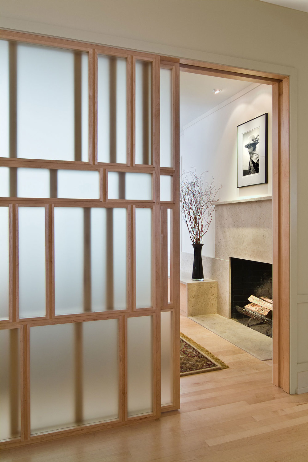 View looking into the living room towards the fireplace. The opaque glass encased by wood creates a partition of space and a focal point for the screen wall. The minimal, stone fireplace complements the simplicity of the screen.