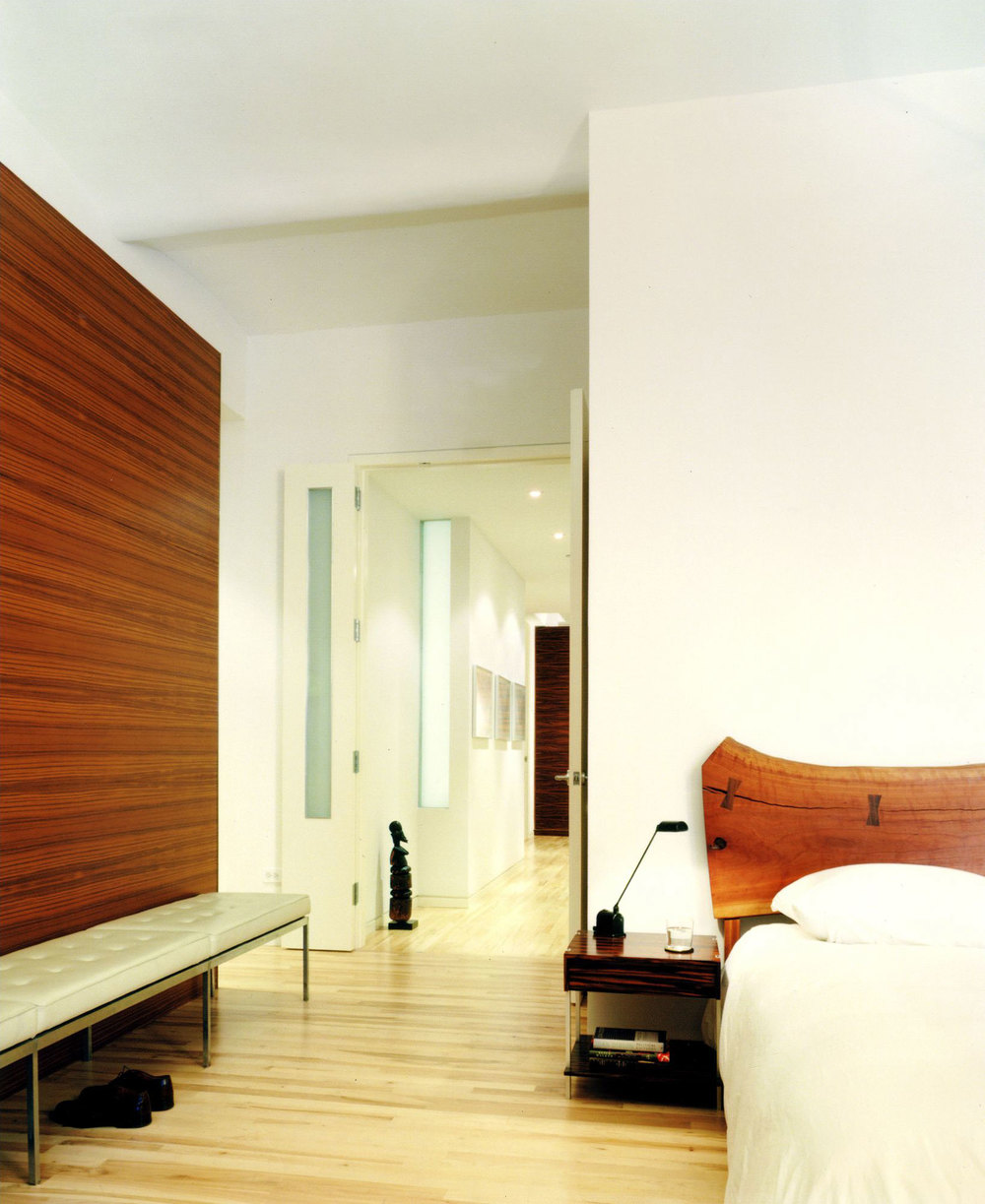The teak wall of the bedroom works together with a white museum zephyr bench and George Nakashima cherry headboard.