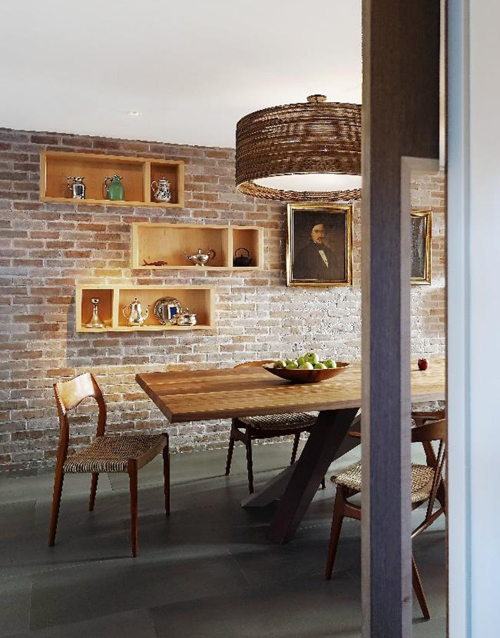 Details of the screen wall against the stair provide a clever solution to space separation.The dining area can be seen with its staggered display shelving units. Graypants Studio Lighting