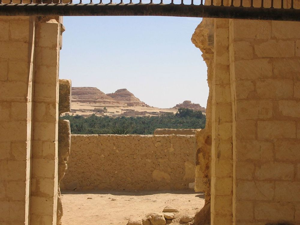 A view from inside the ruins of the Temple of Amun toward the surrounding oasis and desert.