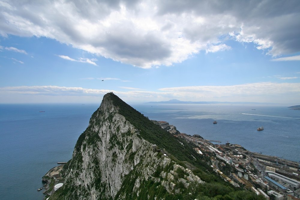 The European Pillar of Hercules: the Rock of Gibraltar (foreground), with the North African shore in the background (Source: Wikipedia).