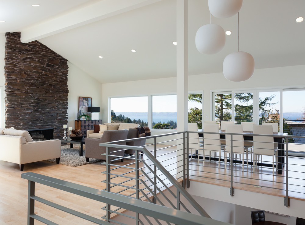 Open-plan living space overlooking Puget Sound. Restoration of original mid-century fireplace and light fixture.