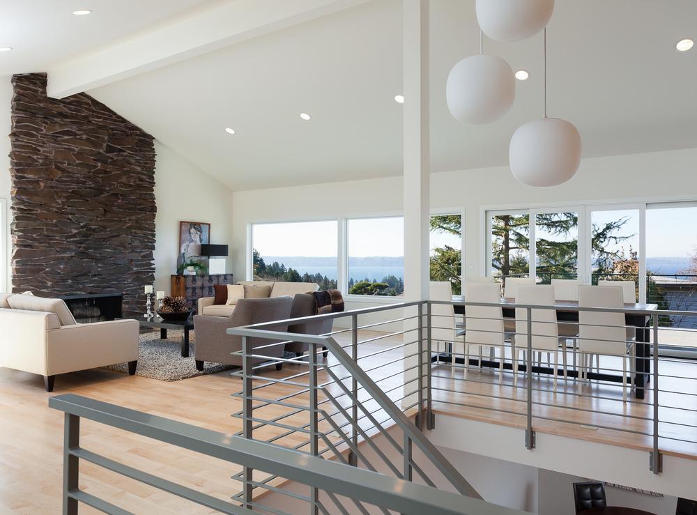 Open-plan living space overlooking Puget Sound. Restoration of original mid-century fireplace and light fixture.