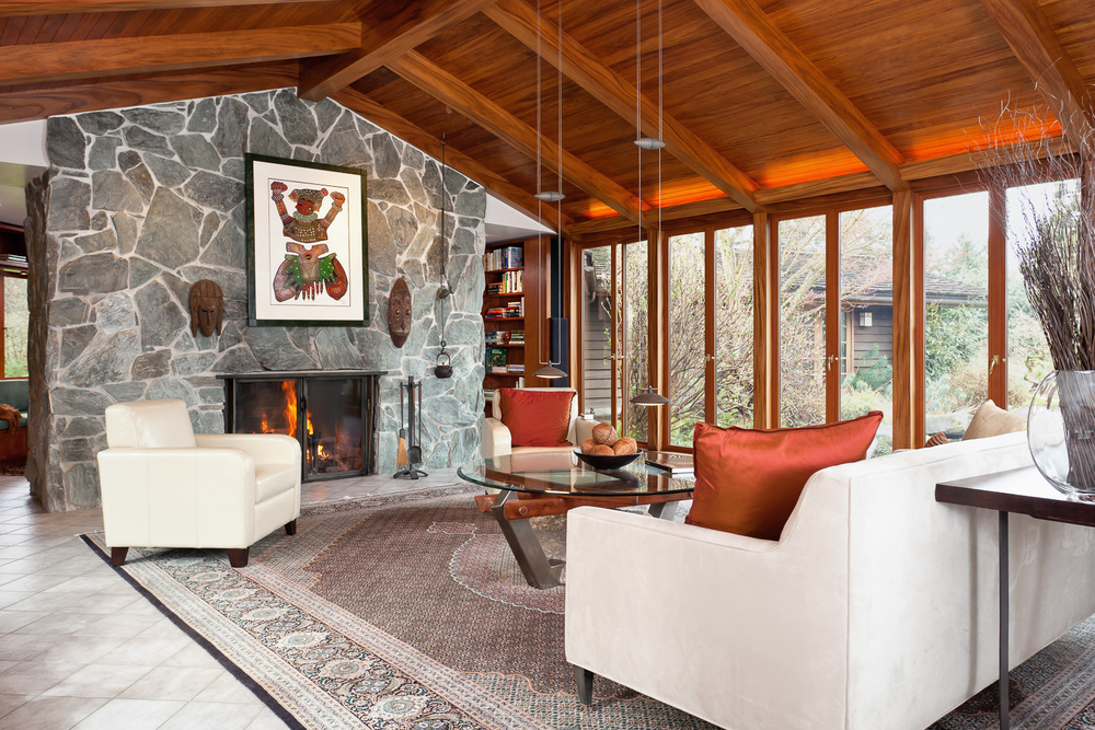 Custom-built stone fireplace, hand-forged fireplace doors, cathedral ceiling with valence lighting. Coval House. Mercer Island, Washington