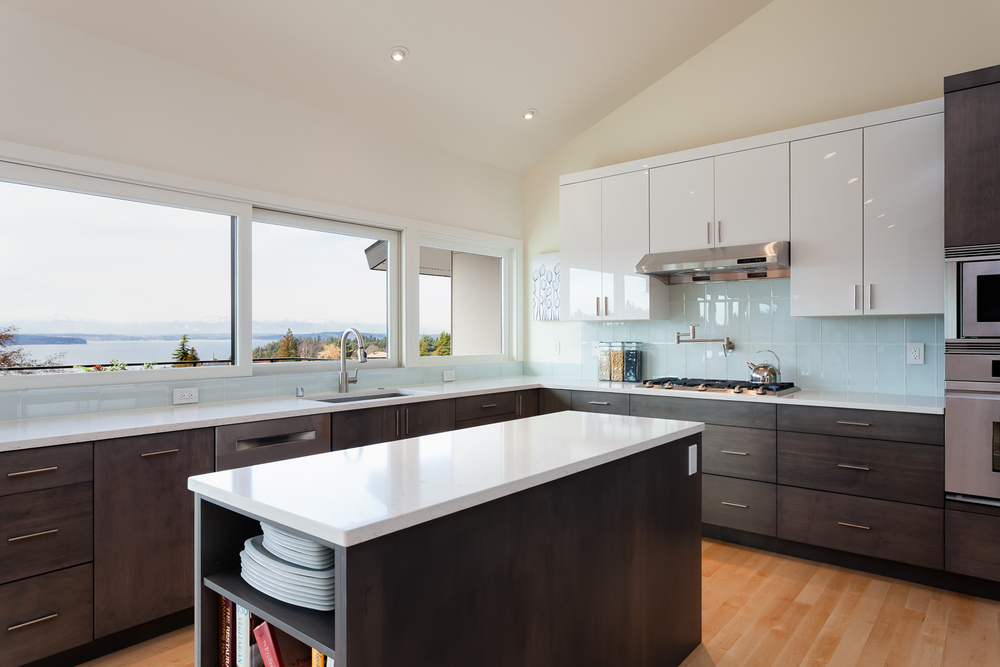 Full-scale remodel of mid-century home. Quartz countertops, stained maple cabinets, maple flooring. Seattle, Washington
