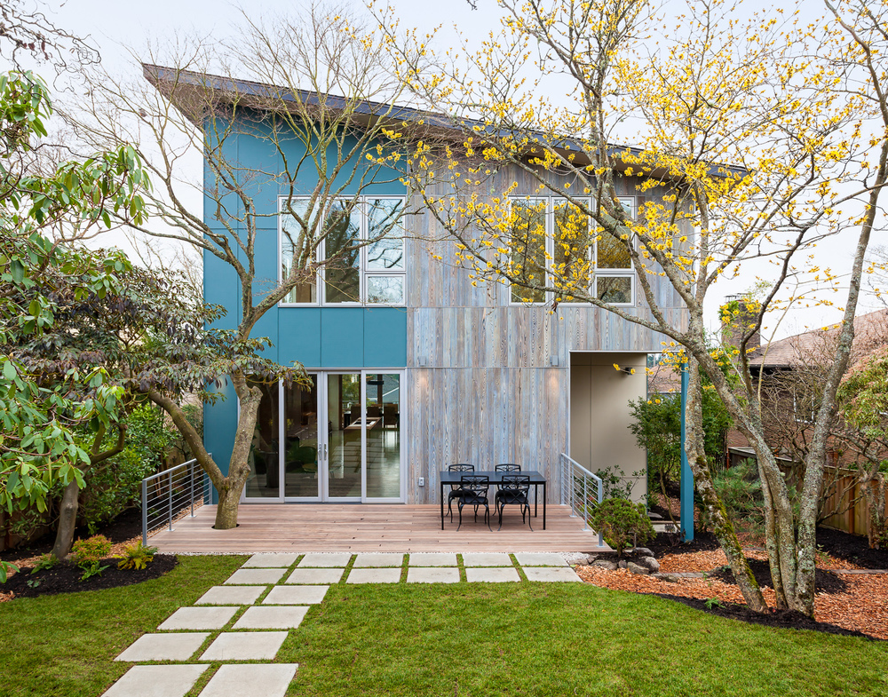 Rear facade and outdoor space of design-build home. Features mature landscaping preserved during construction. Seattle, Washington