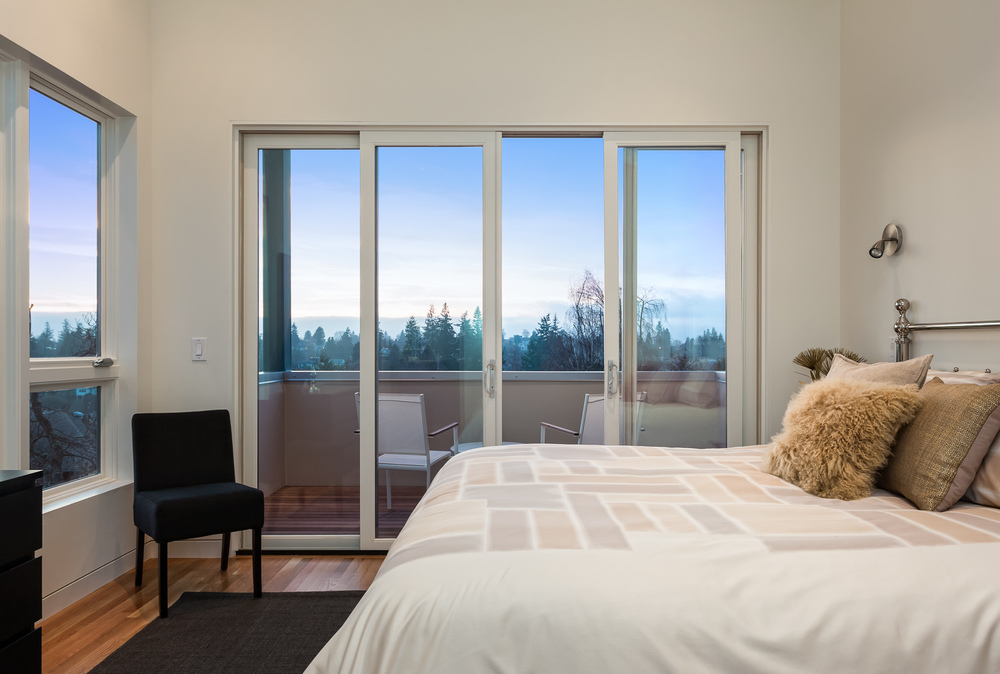 Bedroom, deck, and view in newly-built home. Seattle, Washington