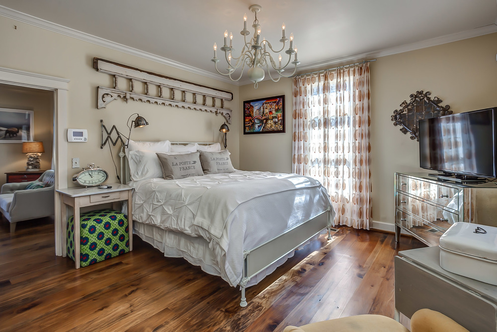 The master suite in the Tin Roof Cottage features a lux cal-king and antique decor as art | Pot N' Kettle Cottages
