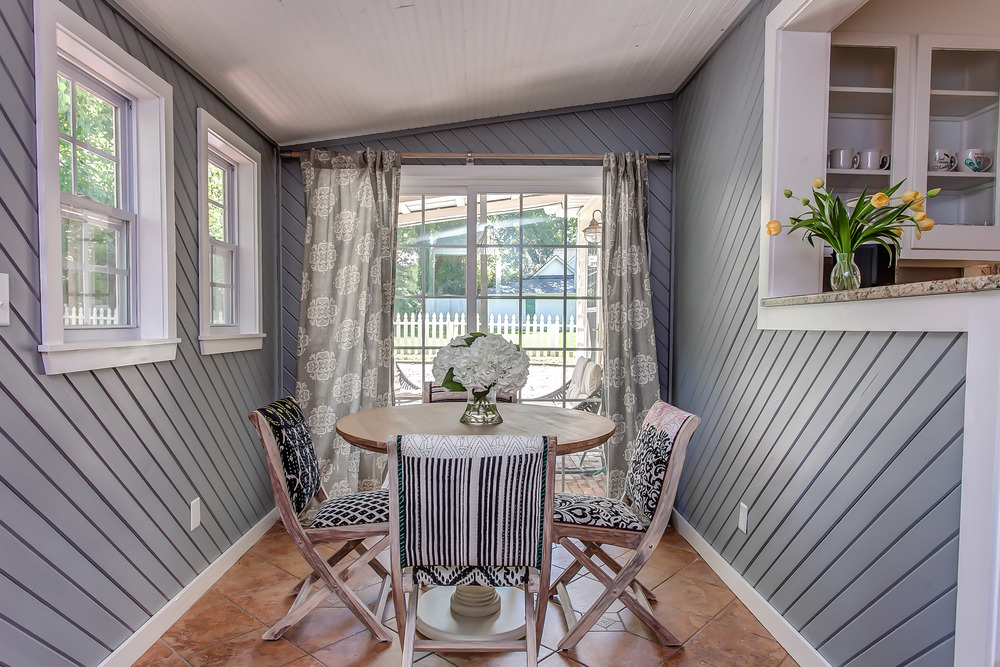 The dining room in the Coda Cottage features a modern farmhouse vibe with classic gray and white modern upholstered chairs | Pot N' Kettle Cottages