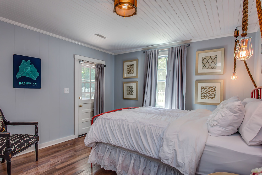 The master bedroom features a lush king size bed and artistic decor | Pot N' Kettle Cottages