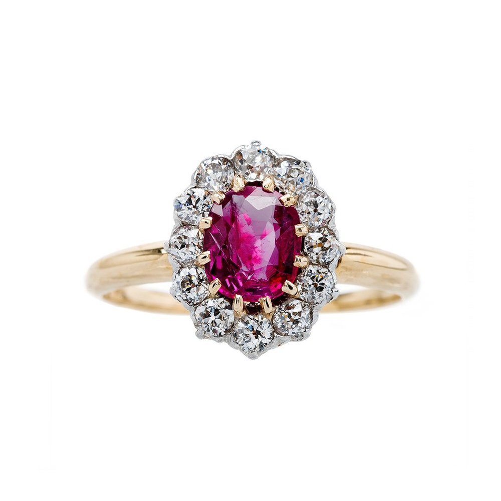 Chelan Way  is a beautiful and authentic Victorian era (circa 1895) platinum topped 18k yellow gold ring. This classic antique ring features an brightly saturated 0.81ct Oval Cut ruby accompanied by a AGL certificate stating the ruby is Unheated with Burmese origin. The slightly purplish red ruby is set with twelve yellow gold prongs. The glittering center stone is further adorned by an oval shaped halo of twelve Old Mine Cut diamonds, totaling approximately 0.40ct in weight, each individually prong-set in platinum. The ring has an extremely low profile and the Burma/No Heat combination makes Chelan Way an incredibly special piece.