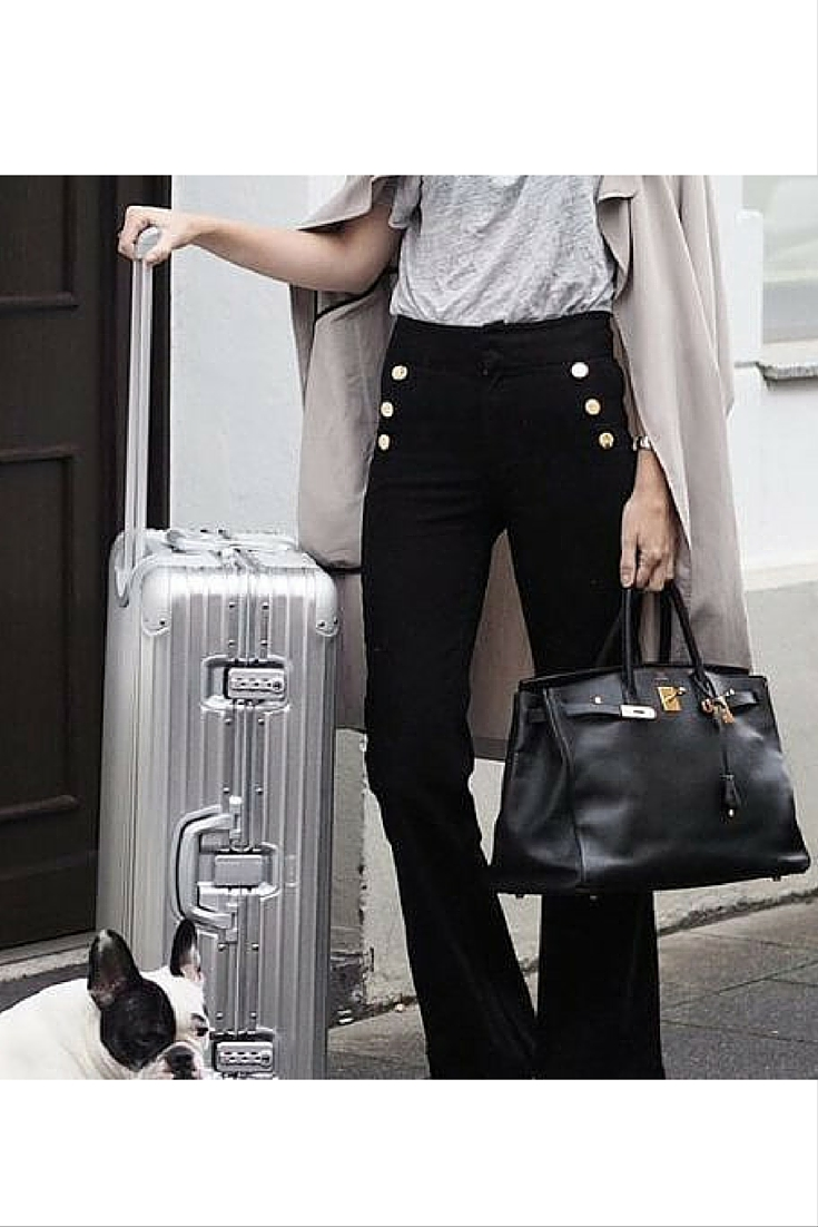 sneakers and pearls, street style, grey tee with black pants and a beige coat, Hermes handbag and rimowa suitcase for a travel companion, jet setter, trending now.jpg
