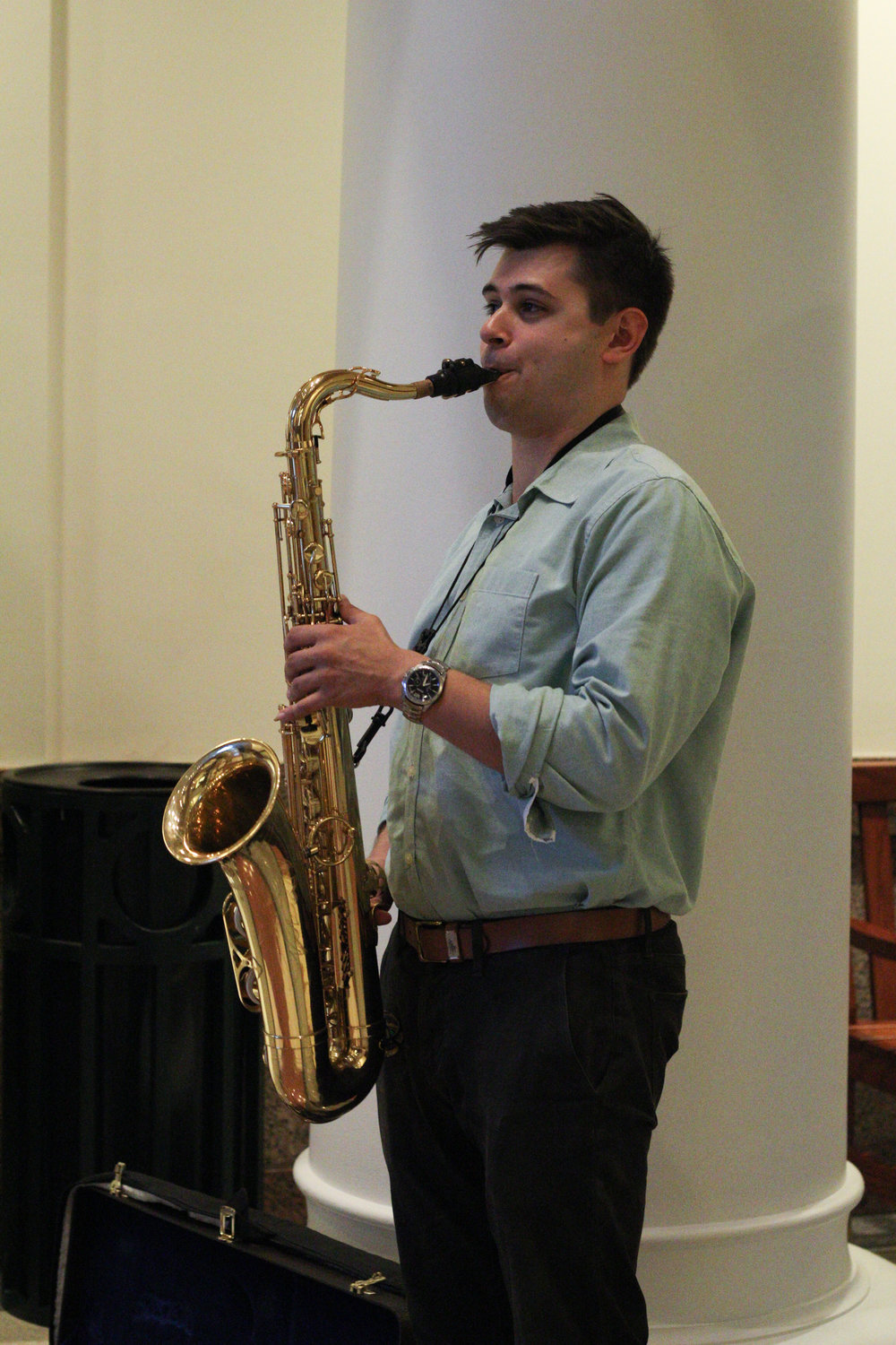Creative Waco intern Michael Incavo plays saxophone outside the reception hall.