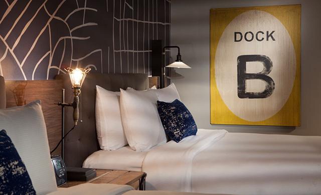 """Double Queen Guestroom with Custom """"Dock B"""" metal signage."""