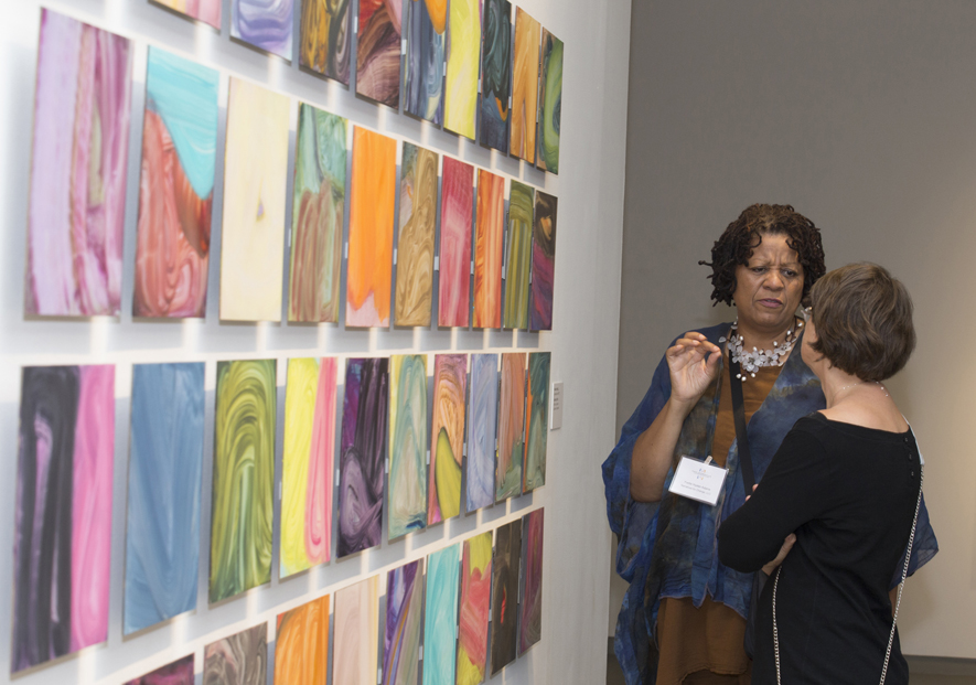 Visitors discuss Fran O'Neill's forty untitled panels at the  Confronting the Canvas  members' preview. Image courtesy of Thomas Hager.