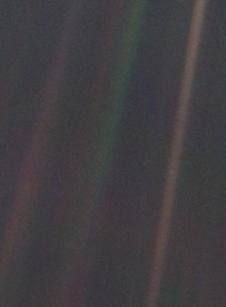 """""""This narrow-angle color image of the Earth, dubbed 'Pale Blue Dot', is a part of the first ever 'portrait' of the solar system taken by Voyager 1. The spacecraft acquired a total of 60 frames for a mosaic of the solar system from a distance of more than 4 billion miles from Earth and about 32 degrees above the ecliptic. From Voyager's great distance Earth is a mere point of light, less than the size of a picture element even in the narrow-angle camera. Earth was a crescent only 0.12 pixel in size. Coincidentally, Earth lies right in the center of one of the scattered light rays resulting from taking the image so close to the sun. This blown-up image of the Earth was taken through three color filters -- violet, blue and green -- and recombined to produce the color image. The background features in the image are artifacts resulting from the magnification."""""""