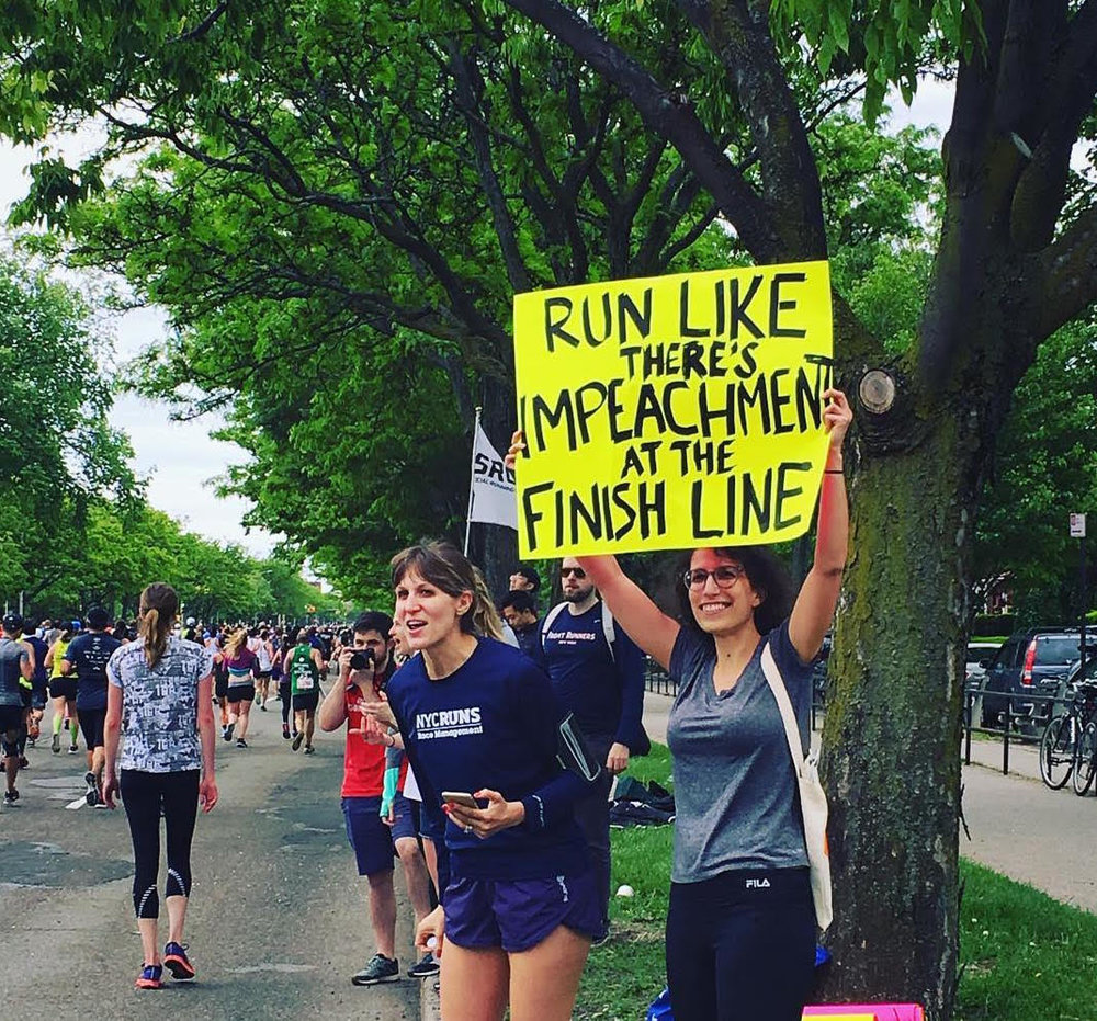 Kara (holding the sign)  near the end of this year's Brooklyn Half Marathon. The promise of impeachment might actually motivate us to run next year!