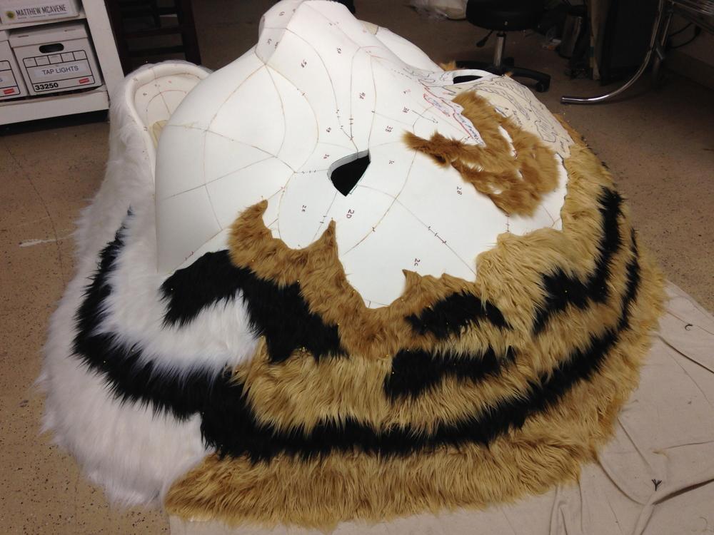 Matthew McAvene covers the tiger head sculpture with fur.jpg