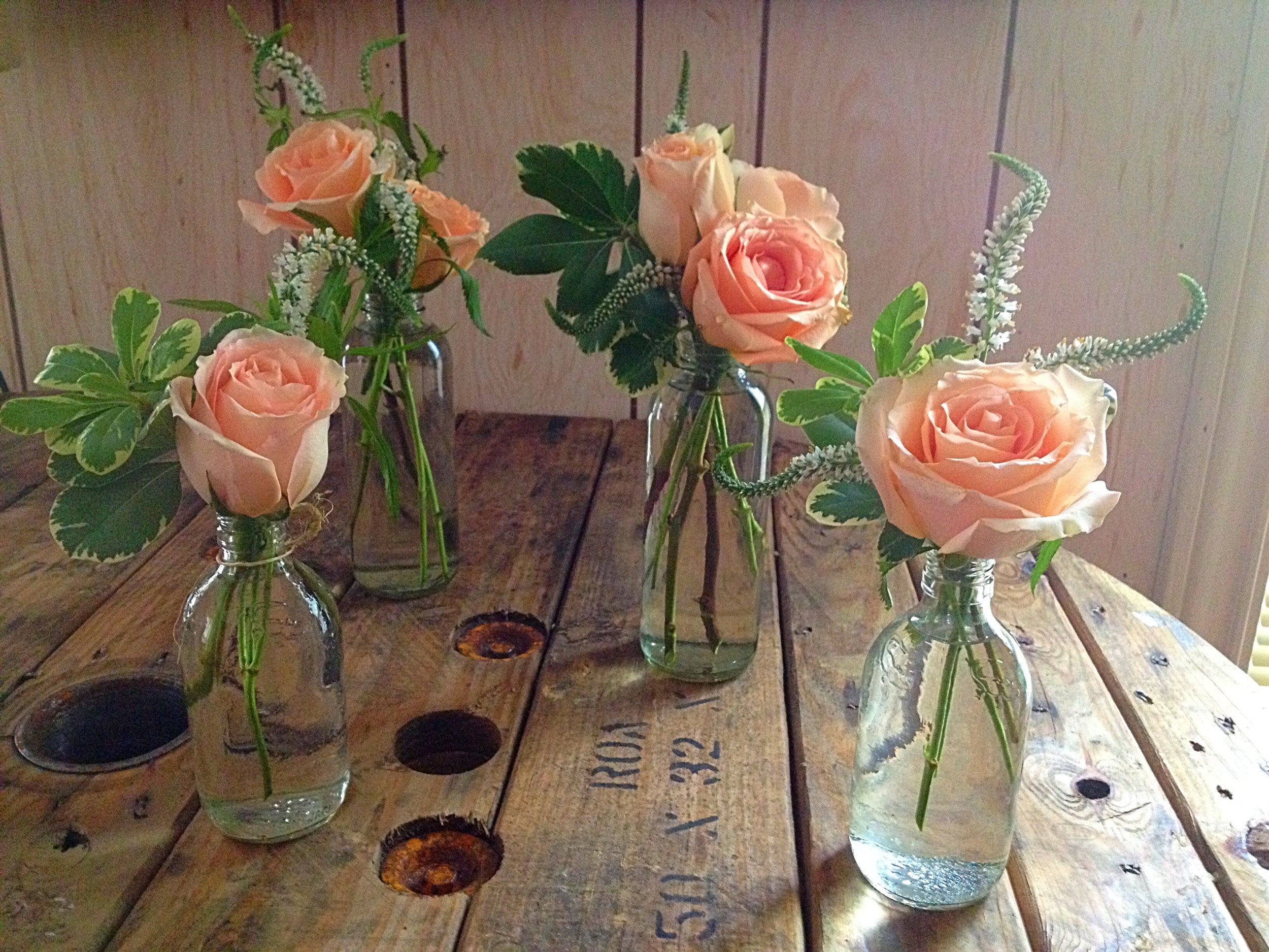 mixed vases with pittosporum, caramel roses and white veronica