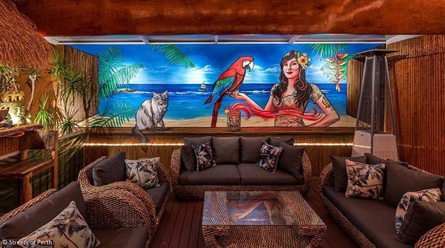 "As the year draws to a close, we thought we'd save 2016's best mural until last. Of course, we're a little biased with this one because... it's ours! 😃 Since starting SoP 2.5 years ago, we've always wanted a mural in our own home, so when we bought a new house that had a ready-made Tiki Bar out back, we instantly knew who to call to transform the main 7m wall - the one and only @Fieldey. So, over the past 12 months, our mural has taken shape in stages and we're very proud to finally present the finished wall! When taking a design brief, we asked Fieldey to paint a ""Trompe L'Oeil"" style beach scene to open up the space, plus a Tiki babe (modelled by the lovely @marinamartini) a pirate ship (with a kraken, naturally), and a little magic to boot. ✨ Fieldey also added Norfolk Island's famous Lone Pine as a nod to her old home in Emily Bay, as well as our beloved cat Indiana. 🌴 🌲 ☠ 🐙 😻 We hope you like our mural anyway, and we'd just like to take this opportunity to wish you all a very Merry Christmas and an amazing 2017! 🍻 We're taking a couple of weeks off now, but we promise to be back in the new year with a ton of new local mural shots to share with you. In the meantime, thank you for all your support this year, and please keep the location tips coming! Lots of love, Nikki & Duncan. xo 🙋🏼🙋🏻‍♂️ #streetsofperth #fieldey #perth #kewdale #perthstreetart #perthartist #ragdollcat #norfolkisland #tikibar #tikibabe #parrot #trompeloeil"