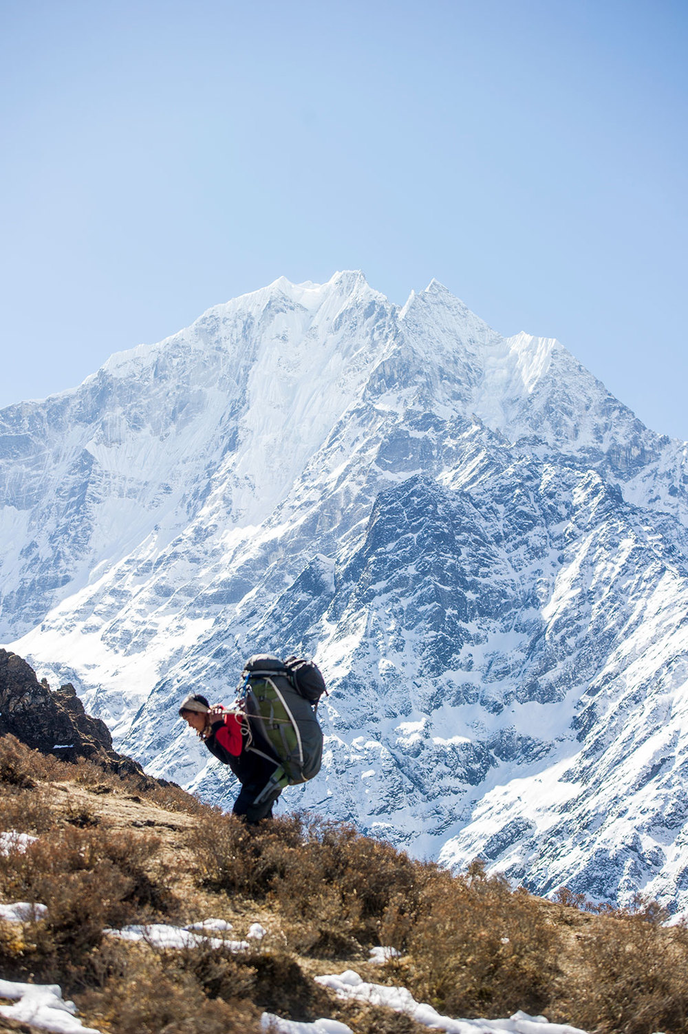 A Sherpa porter carries tourist's bags to Tengboche. Porters are poorly paid, but the only work for many young men.