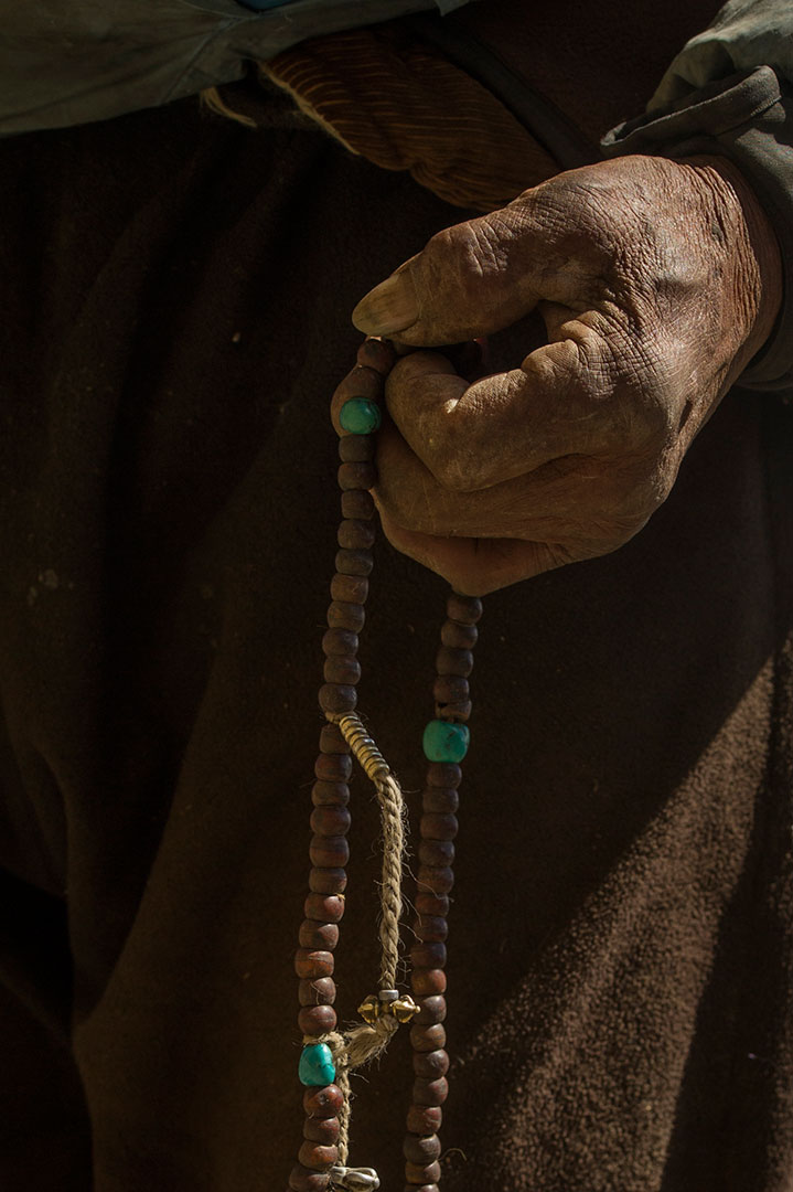 Karma Chhering carries his prayer beads with him as he tends to his yak herd. He is the oldest man in Phortse, and is heavily spiritual.