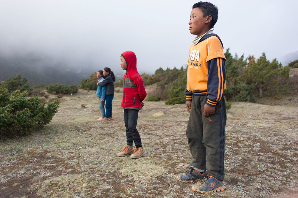 MAY 09, 2015- THAME, NEPAL- A group of kids watch an approaching helicopter, which delivered food to the village for donation.