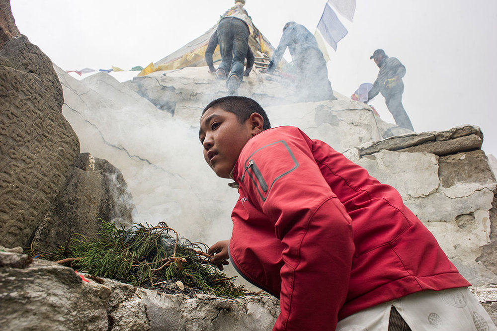 MAY 18, 2015- KUNDE, NEPAL- Members of the Kunde Community Club work to replace prayer flags on the damaged stupa outside of town.