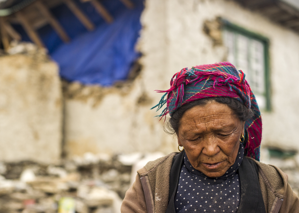 MAY 19, 2015- KUNDE, NEPAL- Lhakputi cleans dishes outside her damaged home.