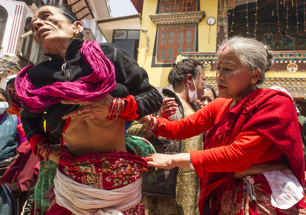A woman begs a faith healer to heal her chronic stomach pains. Many people flocked to faith healers in the area after the earthquake.