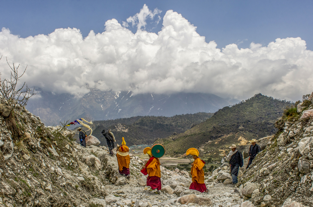 Monks from Kunde Gompa walk across a recent landslide outside Kunde and Khumjung villages during a fertility Puja for good crops.