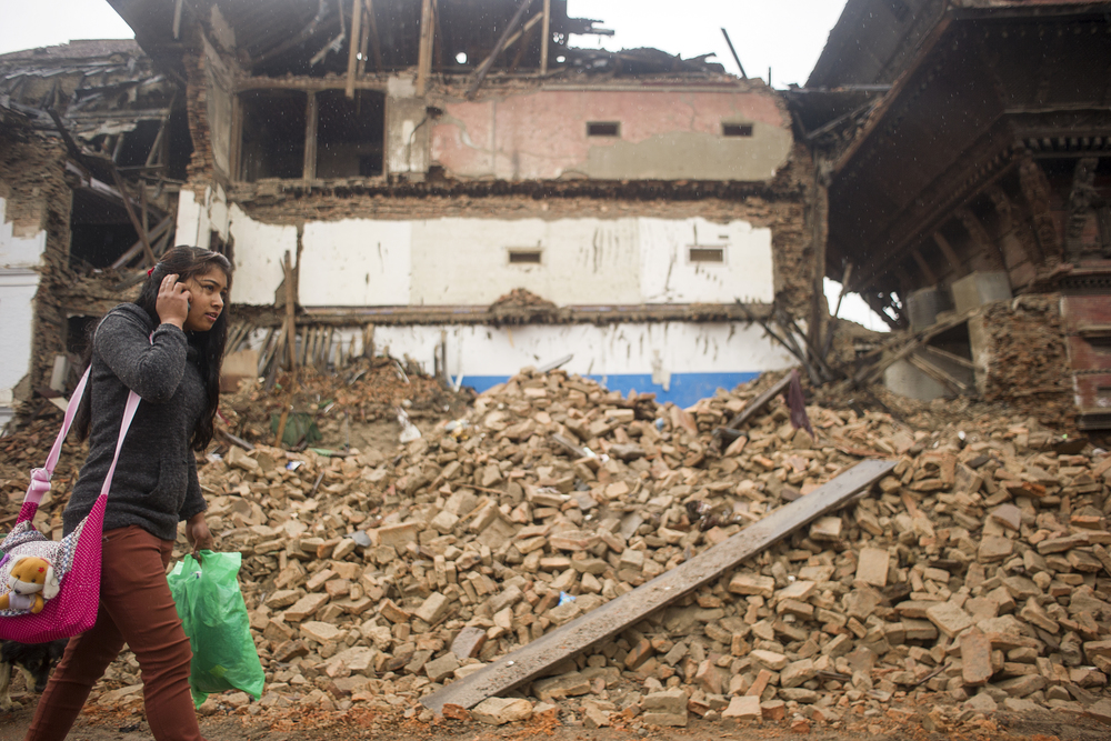 A woman walks past rubble in Kathmandu Durbar Square. The square was badly damaged by the 7.8 Mag. earthquake on April 25, 2015.