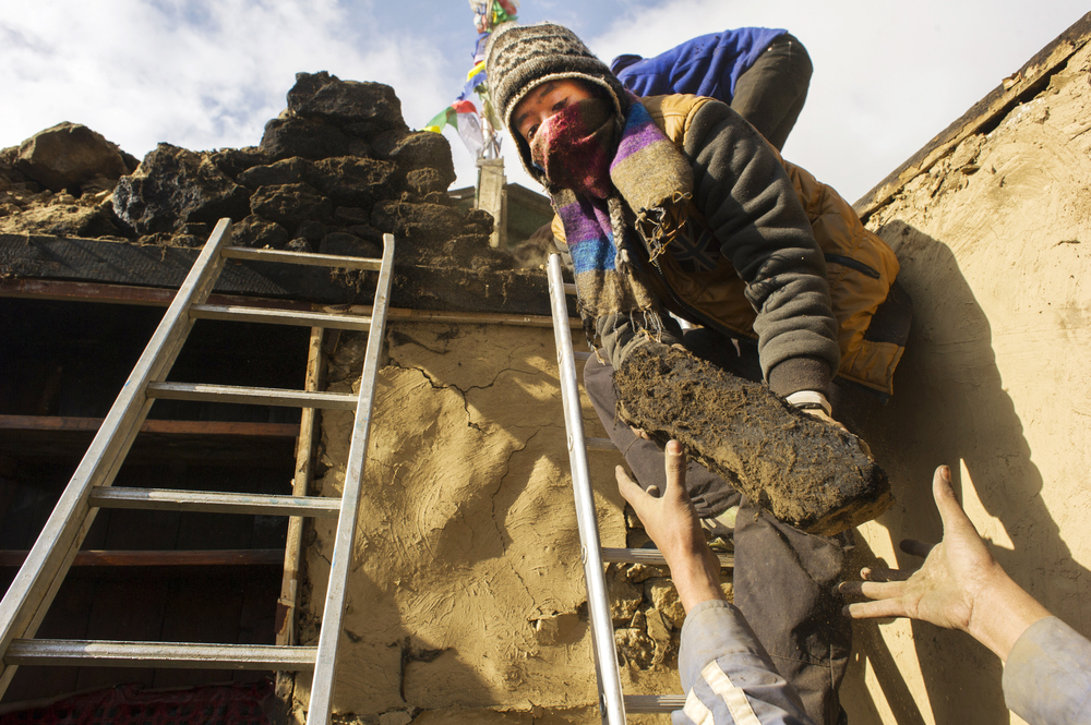 Villagers work to demolish a home damaged in the earthquake. Demolition and construction are done entirely by hand.