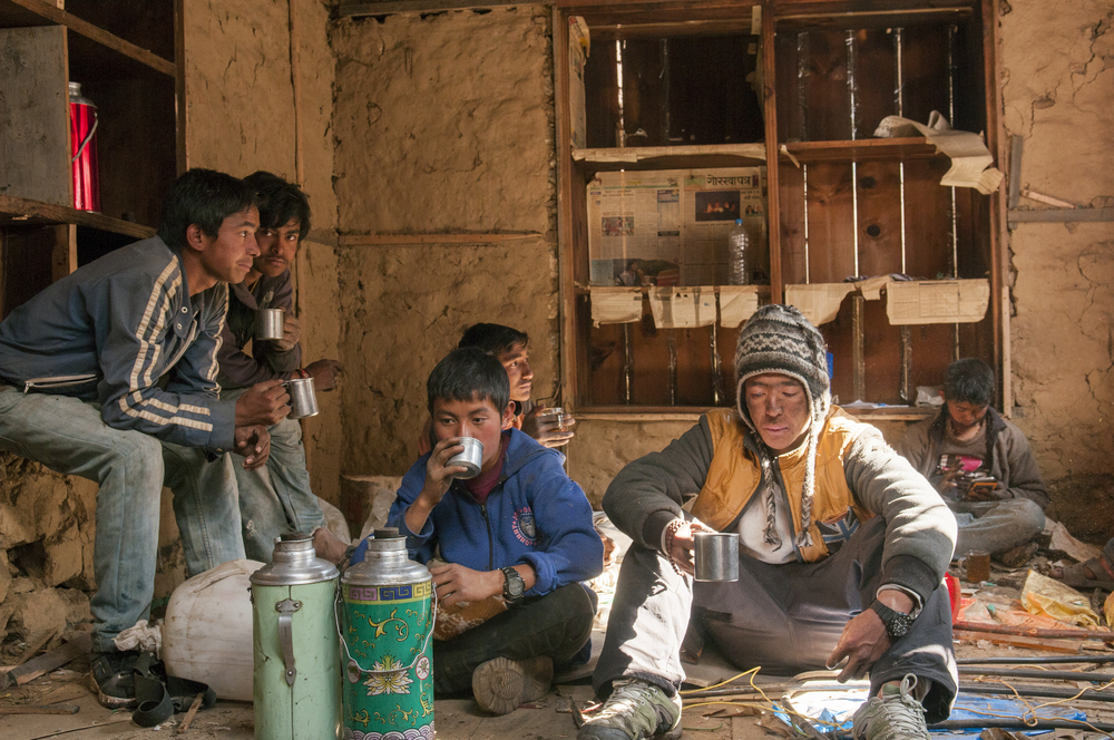A group of workers drink Omeecha (Milk Tea) as they take a break during demolition of a home damaged by the earthquake.