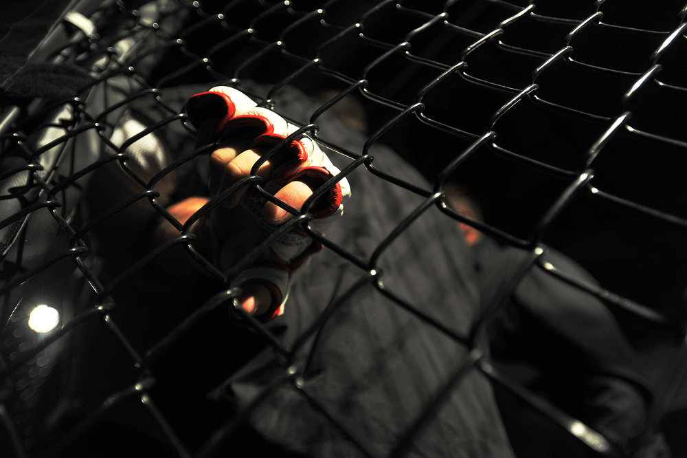 A fighter holds onto the fence for stability as fight officials evaluate him for a concussion.