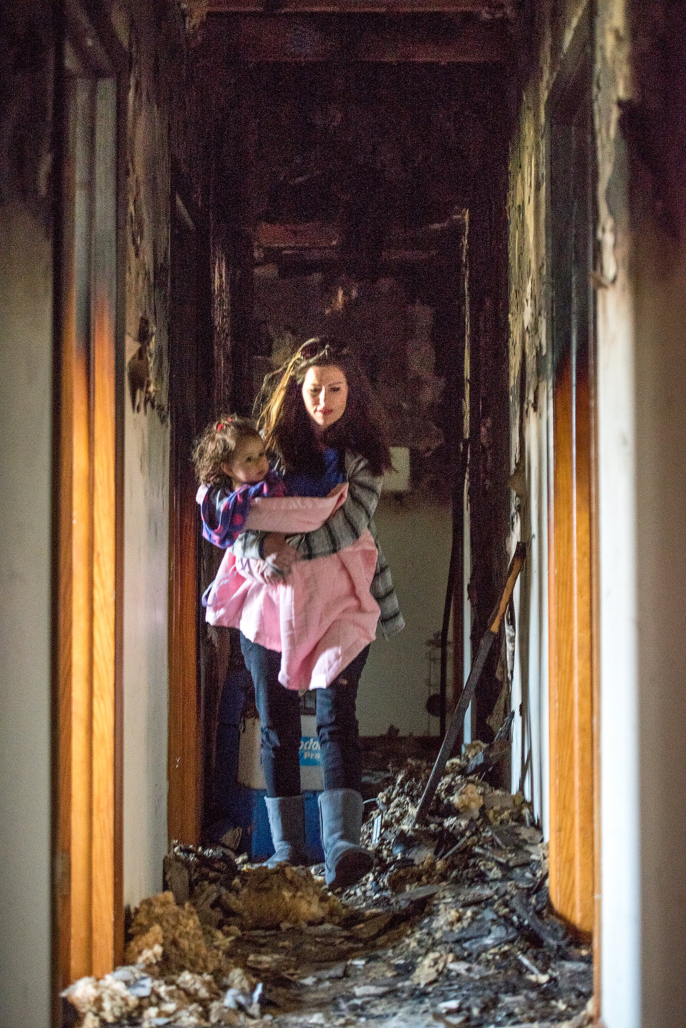 Donna Conley carries her daughter, Presley, through the charred hallway of her home in the Church of Christ Thursday afternoon.