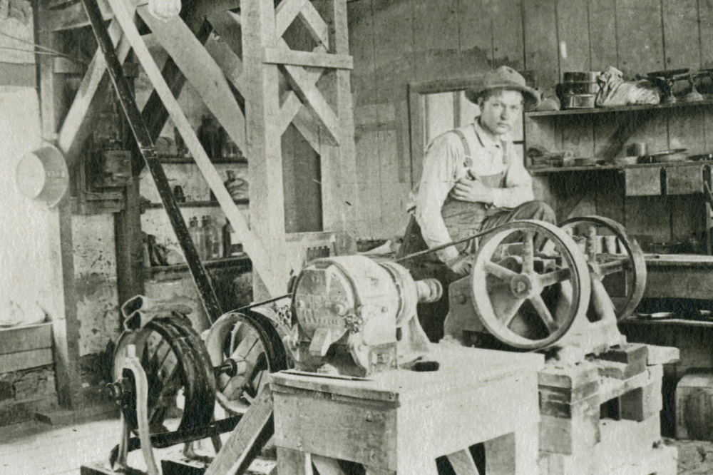 Leslie B. Duke beside the crusher, Assay Lab, 1913